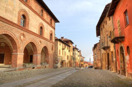 saluzzo: Paved street among old historic houses in town of Saluzzo, northern Italy. Stock Photo