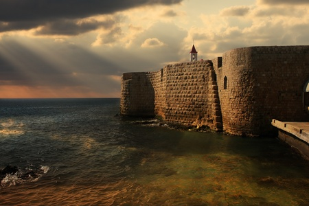 View on Mediterranean sea and ancient walls of Acre at sunset in Israel. 에디토리얼