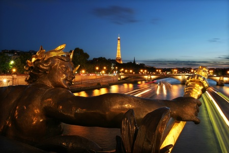PARIS - JULY 09: View on Seine river, illuminated Eiffel Tower and sculpture on Alexander the III bridge at evening on July 09, 2007 in Paris, France.