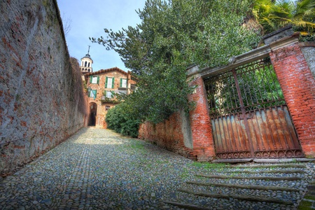 Old rusty gate and narrow paved street in town of Saluzzo, northern Italy. Stock Photo - 11962888