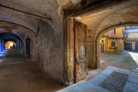 saluzzo: Vintage door to small courtyard and ancient passage in town of Saluzzo, northern Italy.