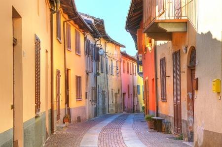 古い多色家イタリア北部ピエモンテ州セッラルンガ ・ ダルバの町の間の狭い舗装された通り。
