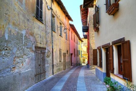 empedrado: Angosta calle pavimentada entre vieja casa abandonada de un lado y renovado de otros en la ciudad habiente de Serralunga d'Alba, en el norte de Italia.