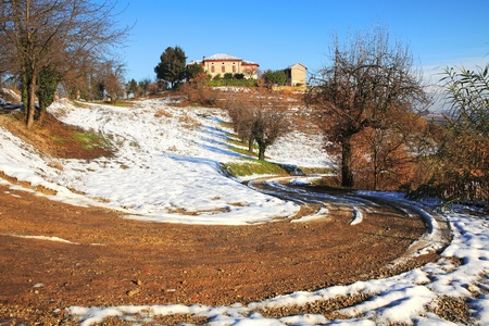 unpaved road: Countryside unpaved road among snowy hills of Piedmont, northern Italy.