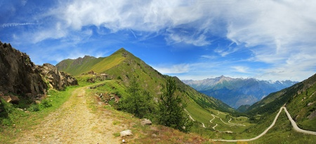 unpaved road: Panoramic view on unpaved road among hills and peaks of Alps, Italy.
