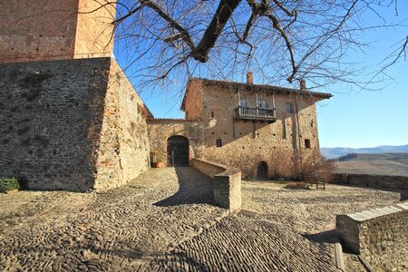 stoned: Paved stoned courtyard, old brick house at the entrance to castle in town of Serralunga D