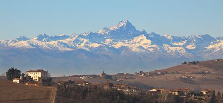 european alps: Panoramic view on small village on the hills against Alp mountains with snowy peaks in Northern, Italy. Stock Photo