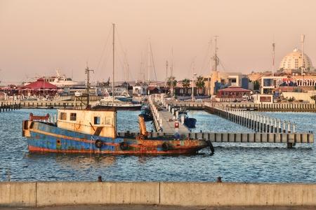Old rusty fishing ship float on water surface in marina on Mediterranean sea, Israel  photo