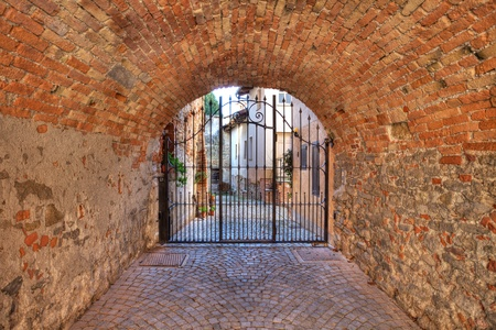 Old brick arched passage leading towards metal gate at the entrance to courtyard in La Morra, Italy  photo