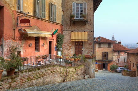 Horizontal image of narrow stone paved street among multicolored houses in town of Saluzzo, Northern Italy
