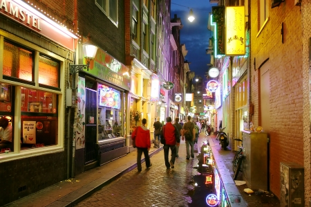 AMSTERDAM - JULY 17: Bars and coffee shops on the street full of tourists at night in famous Red Light District in Amsterdam, Netherlands.