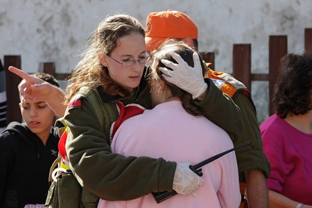 ASHKELON - JANUARY 10: An israeli soldier from the rescue team holds and hugs young girl who was witness of missile launched by Hamas terrorists from Gaza explode near her house on January 10, 2009 in Ahskelon, Israel. Stock Photo - 12592191