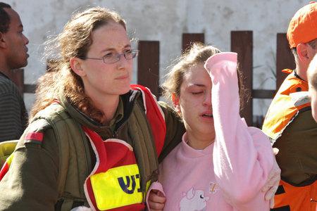 zeugnis: Ashkelon - 10. Januar: Ein israelischer Soldat aus dem Rettungsteam h�lt und umarmt jungen M�dchens, das von Raketen durch die Hamas-Terroristen aus dem Gazastreifen explodieren in der N�he ihres Hauses am 10. Januar 2009 in Ahskelon, Israel ins Leben gerufen wurde Zeuge. Editorial