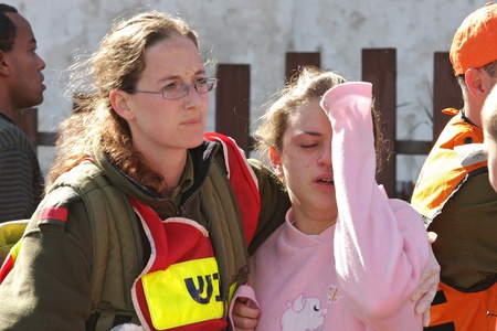 ASHKELON - JANUARY 10: An israeli soldier from the rescue team holds and hugs young girl who was witness of missile launched by Hamas terrorists from Gaza explode near her house on January 10, 2009 in Ahskelon, Israel.