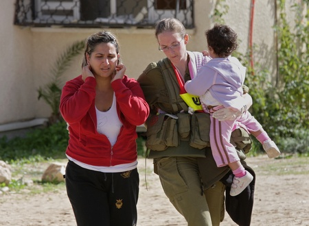witness: ASHKELON - JANUARY 10: An israeli soldier from the rescue team holds young girl who was witness of missile launched by Hamas terrorists from Gaza explode near her house on January 10, 2009 in Ahskelon, Israel.