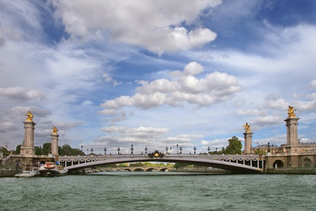 alexander: View on famous Alexander The Third bridge  aka Pont Alexandre III  over Seine river under beautiful blue sky with white clouds in Paris, France