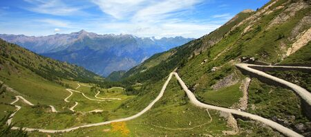 unpaved road: Panoramic view on unpaved road running through the hills and mountains of Alps in northern Italy