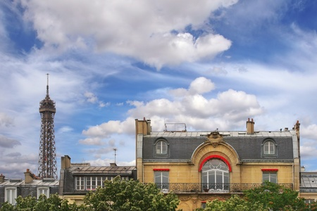 Residential house top floor and mansard exter view and fragment of Eiffel Tower under beautiful blue sky with white clouds in Paris, France  Stock Photo - 13082805