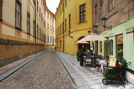Old street with small hotel and outdoor restaurant in historic part of Prague.