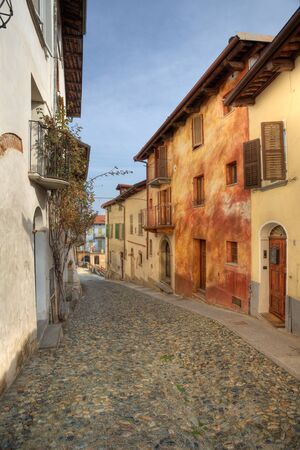 Vertical oriented image of narrow paved street among old multicolored houses in town of Saluzzo, northern Italy. Stock Photo - 13214357