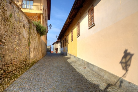 Narrow paved street among old houses and wall in town of Saluzzo, northern Italy. photo