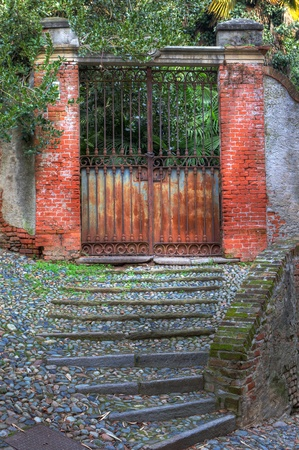 saluzzo: Vertical oriented image of old rusty gate in the entry to garden and narrow paved stairs in town of Saluzzo, northern Italy