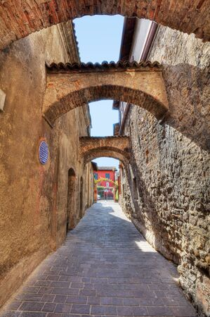 sirmione: Vertical oriented image of arched pathway among ancient brick walls in Sirmione, Northern Italy