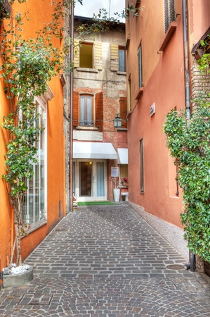 narrow street: Vertical oriented image of narrow stone paved street among colorful buildings in Sirmione, Northern Italy  Stock Photo