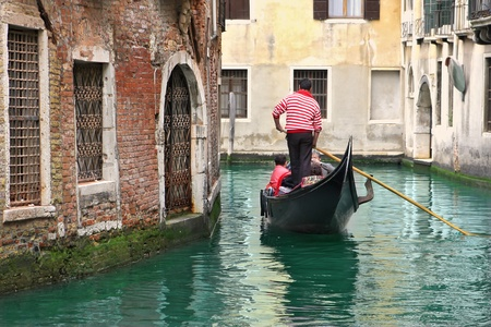 romantically: Venetian canal and gondola among old houses in Venice, Italy  Stock Photo