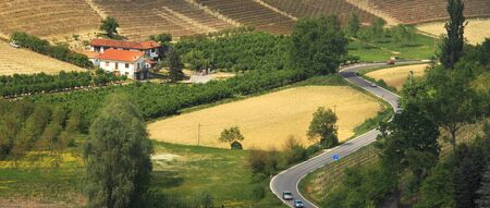 Panoramic view on lone house and serpentine road among hills of Piedmont, northern Italy  photo