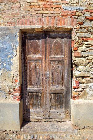 Vertical oriented image of old wooden door in brick house in town of Serralunga D photo