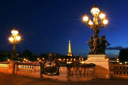 PARIS - JULY 10, 2007: Famous Eiffel Tower with night illumination and beautiful lampposts on Alexander the Third (Alexander III) bridge on July 10, 2007 in Paris, France.
