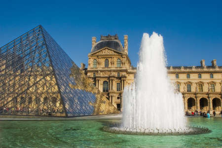PARIS, FRANCE - OCTOBER 07 2007: Famous glass pyramid and big fountain in front of Louvre royal palace (Louvre museum) October 07, 2007 in Paris France.