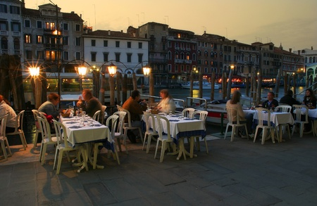VENICE - APRIL 14: People sitting in small outdoor restaurant  on Grand Canal near Rialto Bridge  at evening on April 14, 2005 in Venice, Italy.