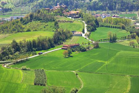 Aerial view on green fields, rural houses and small village at spring in Piedmont, Northern Italy  photo