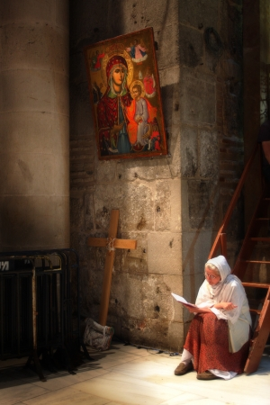 sepulcher: JERUSALEM, ISRAEL - APRIL 02: Unidentified palmer sitting on the stairs under the icon and reading Holy Bible during Easter mass in the Church of the Holy Sepulcher April 02, 2010 in Jerusalem, Israel.