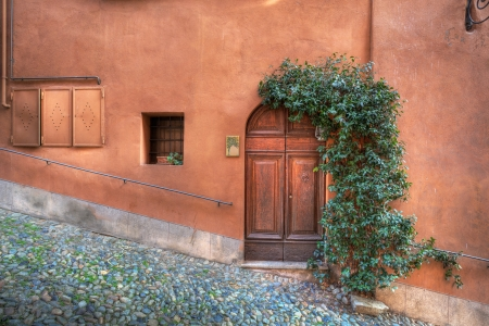 Wooden door, small window in the house with rusty colored wall on small paved street in Saluzzo, northern Italy  Standard-Bild