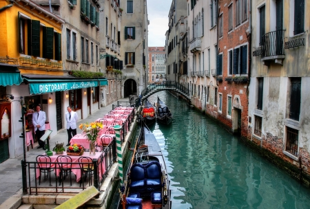 Small romantic restaurant on venetian canal at evening in Venice, Italy