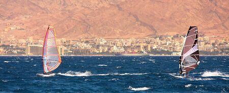 Two surfers on windsurfing boards gliding on surface at the Red Sea in Eilat, Israel  photo