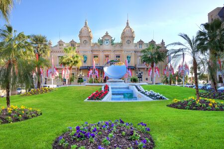 notable: MONTE CARLO - NOVEMBER 17: Exterior view on facade of most famous and notable casino building and beautiful lawn with flowers in front of it on November 17, 2009 in Monte Carlo, Monaco. Editorial