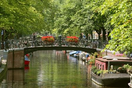 運河オランダ、アムステルダムのアムステル川の花と自転車の小さな橋の眺め
