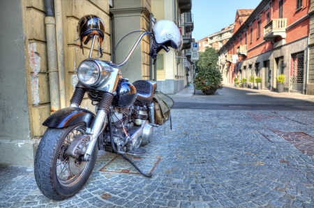 alba: big motorcycle stands on cobbled street of Alba in Piedmont, Northern Italy  Stock Photo