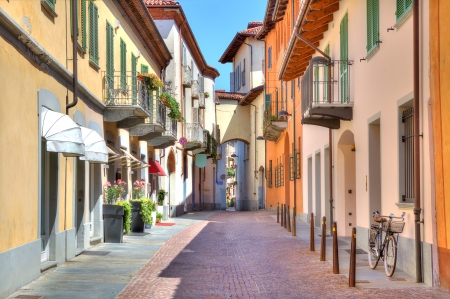 city street: Narrow stone paved street among colorful houses in town of Alba in Piedmont, Northern Italy  Stock Photo