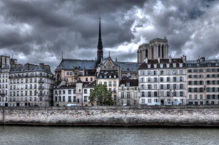 notre dame de paris: Traditional parisian building along Seine river and Notre Dame de Paris Cathedral on background in Paris, France