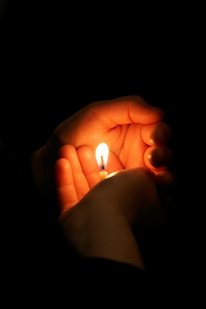 prayer candles: Small candle in the hands of prayer during Easter mass in Jerusalem