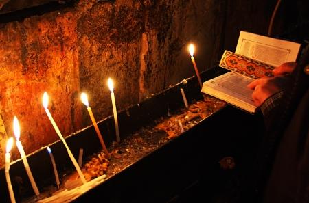 イスラエル、エルサレムの聖墳墓教会で聖書で蝋燭および祈りの手 写真素材