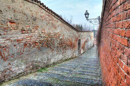 saluzzo: Small narrow street among old walls in Saluzzo, northern Italy  Stock Photo