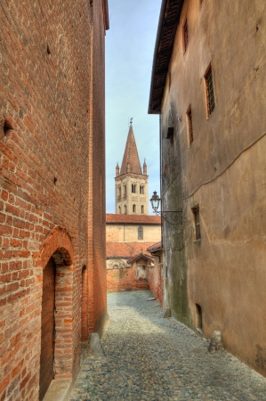 Vertical oriented image of narrow paved street among old historic houses in Saluzzo, northern Italy  photo