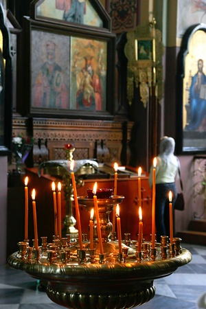 middle easter: jERUSALEM - APRIL 23: Candles and unidentified prayer standing in front of icon in Russian Orthodox Church in Jerusalem, Israel on April 23, 2006. Editorial