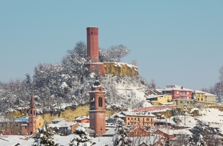 Churches, houses and ancient castle tower covered by snow in small town of Corneliano D photo
